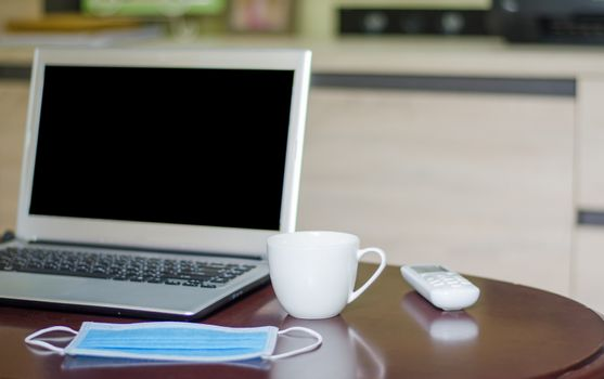 Sanitary masks and laptops on a wooden table, the idea of ​​working at home