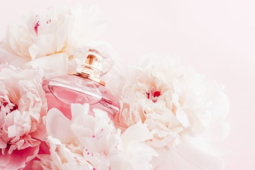 Luxe fragrance bottle as girly perfume product on background of peony flowers, parfum ad and beauty branding
