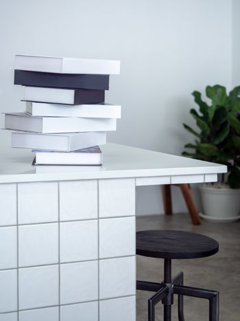 stack of black and white mockup books on white counter bar with wooden bar stool and green leaves in pot in white cafe background minimal style, vertical style.