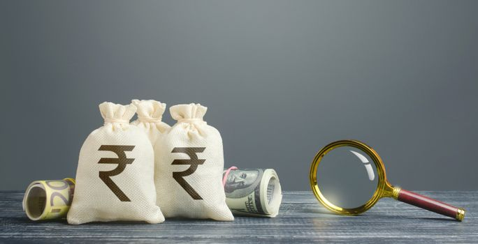 Indian rupee money bags and magnifying glass. Profitable investment, dividends payouts. Financial monitoring of suspicious cash transactions. Search sources of financing projects. Budget revision