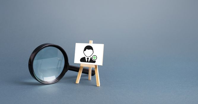 Magnifying glass and an easel with a new hired employee. Recruiting and HR management. Hiring new workers, staffing. Headhunters and Human Resources. Search for skilled specialists and professionals.