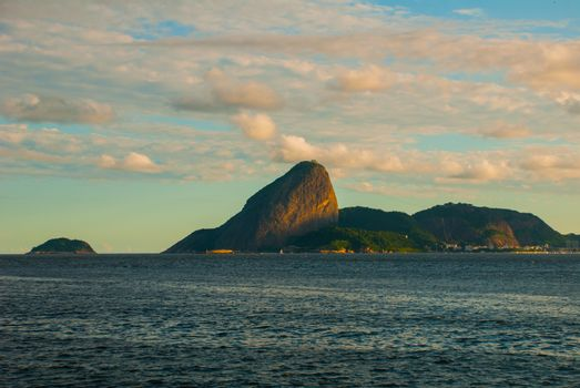 Classic daytime scenic view of Sugarloaf Mountain, Pao de Acucar, standing above Botafogo Bay and Urca district, traditional and wealthy residential neighborhood of the city of Rio de Janeiro, Brazil