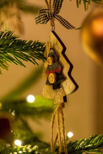 A wooden tree shaped Christmas Tree Decoration hanging from a tree