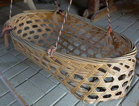An old infant crib suspended by ropes and made from bamboo strips