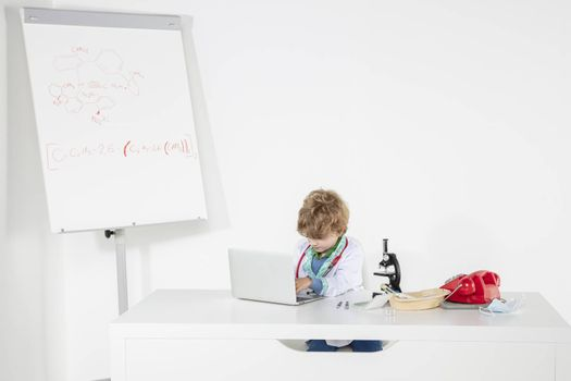 young doctor works on the computer, sits at a desk in his office