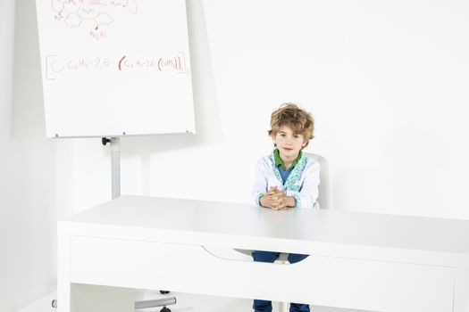 young doctor is sitting behind the desk in his doctor's office