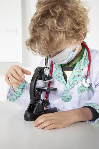 young doctor sitting over a microscope in his laboratory