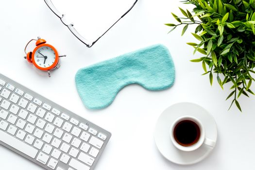 fatigue concept. Sleep mask on white office desk from above
