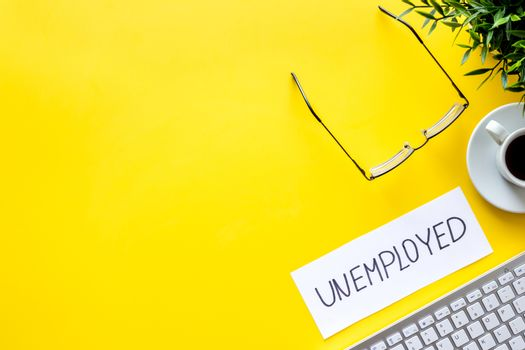 Unemployment - fired, lose job - yellow office desk from above copy space