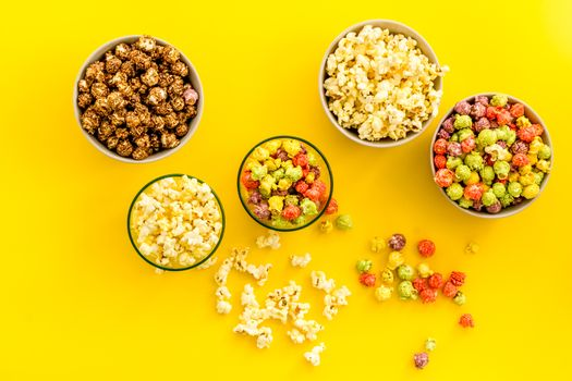 Flavored popcorn on yellow background top view