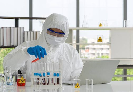Epidemiological researchers in virus protective clothing mixing chemicals according to formulas obtained from computers. Working atmosphere in chemical laboratory.