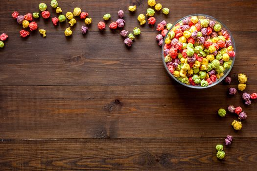 Flavored popcorn on wooden background from above copy space
