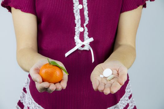 Vitamins from fruits or medicines? A young woman in burgundy paj