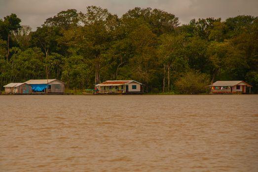 Wooden house on the river bank, Amazon River, rainy season. Amazon river, Amazonas, Brazil, South America