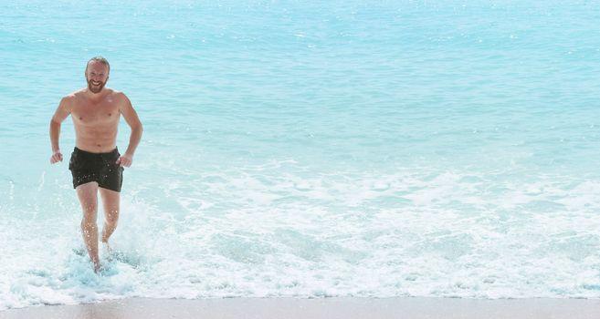 Happy man running from sea