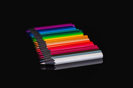 many colored pencils of different colors on an isolated black background with reflection