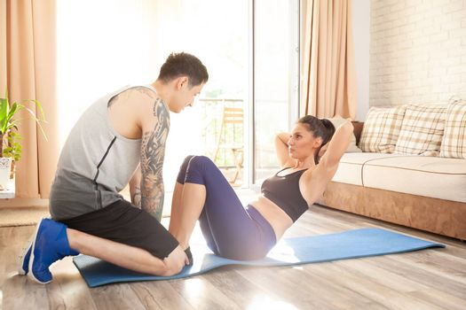 Young couple having a fitness session at home in theie apartment.
