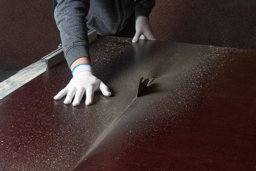 the master saws a brown building shield. master saws plywood on a circular saw. Cutting moisture-proof marine plywood