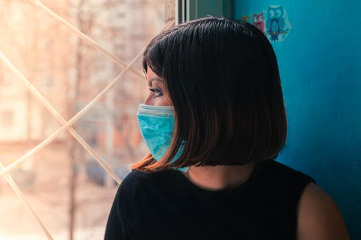 brunette girl in a black dress sits in a surgical  mask sits on a hospital window and looks outside