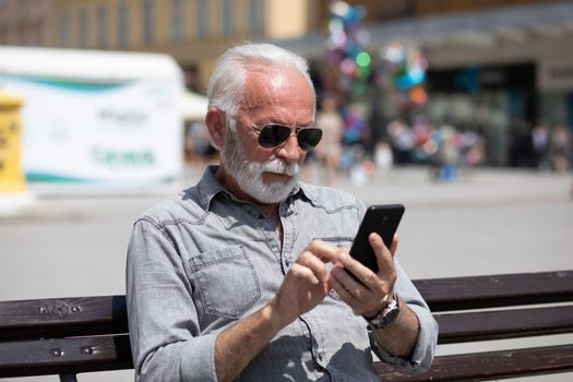 Old man use internet application on smartphone, seating on bench