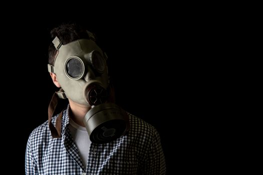 man in a gas mask on a black background. copy space.