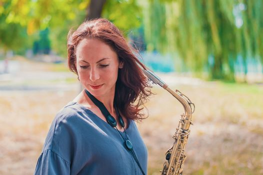 Close portrait of a young red-haired woman in a green park with a saxophone in summer
