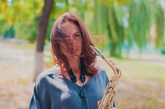 beautiful red-haired girl in a blue jacket with a saxophone in windy weather
