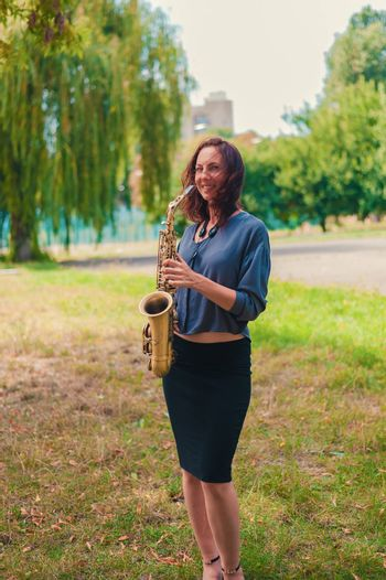 cute young redhead woman in blue blouse and black skirt posing with saxophone in the park