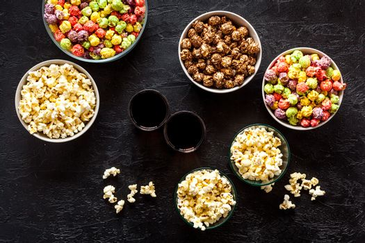 Set of flavored popcorn and soda on black table from above