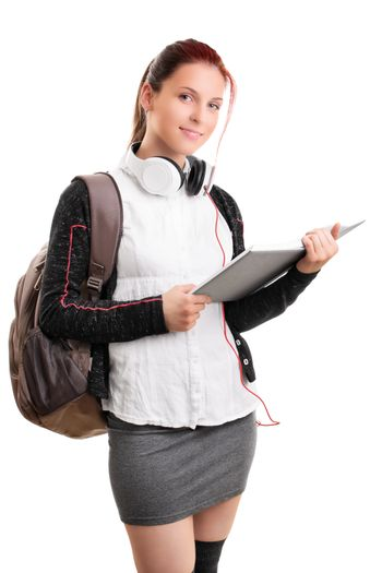 Beautiful smiling young girl in schoolgirl uniform with backpack and headphones, holding an open book, isolated on white background. Student ready for class. Education concept.