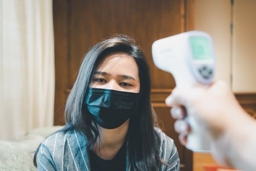 Asian woman wearing mask respiratory protection mask against epidemic flu covid19 or corona virus and body temperature health check measure fever levels by digital infrared thermometer for healthcare