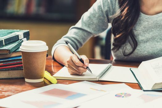 Closeup Asian young Student hand writing homework in library of university or colleague with various book and stationary with coffee cup on wooden table over the book shelf background,Back to school