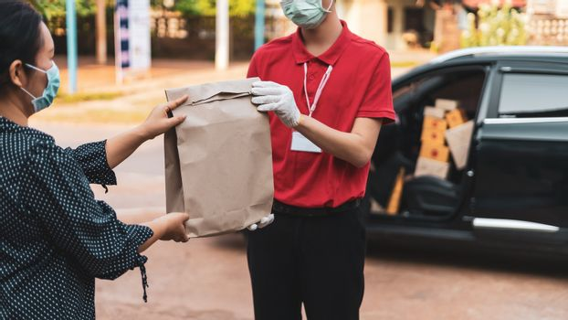Delivery personnel deliver goods to customers during the Covid-19 virus epidemic around the world,Therefore must wear a mask to prevent the spread of the disease,Online shopping and Express delivery . Quarantine