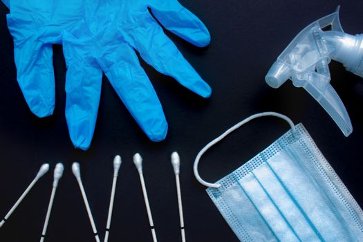 A close up of medical items: throat swabs, gloves, medical face mask and spray disinfecting liquid spray on a black background.