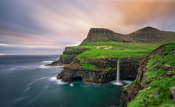 Gasadalur village and its iconic waterfall, Vagar, Faroe Islands, Denmark. Long exposure.