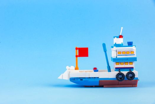 A fishing boat toy isolated on a blue background.
