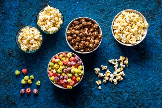 Flavored popcorn on blue desk from above