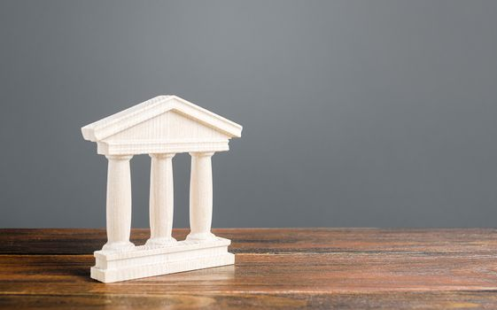 White building figurine with pillars in antique style. Concept of city administration, bank, university, court or library. Architectural monument in old town part . Banking, education, government.