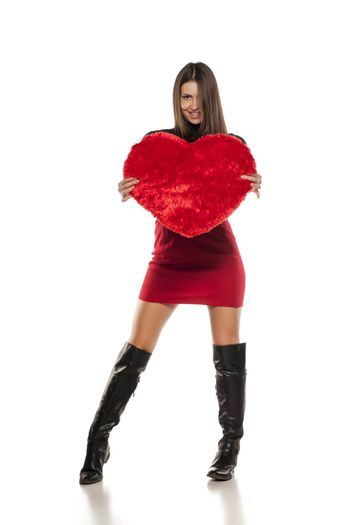 A young woman posing with a velvet pillow heart shape