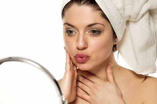 Satisfied young beautiful woman with towel on her head  looking