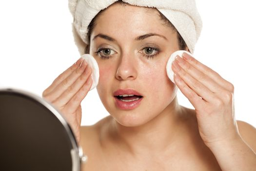 woman removing makeup with the cotton pads