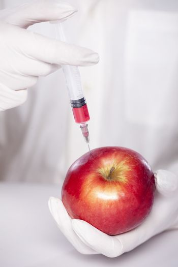 injection of some liquid in red apple