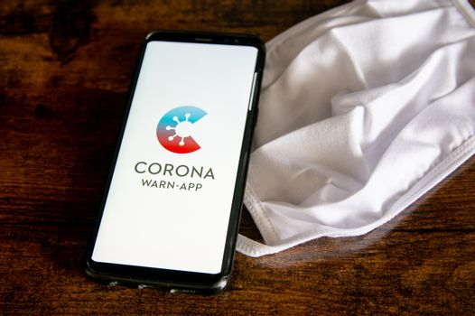 Zittau, Saxony / Germany - June 4th 2020: German Corona Virus Warn App for COVID-19 tracing with white face mask on wooden surface. The new normal, items for everyday life in 2020