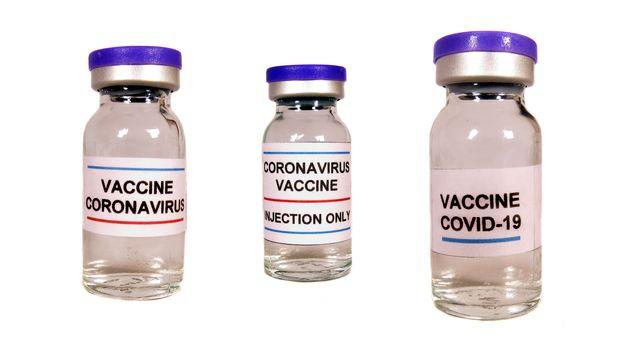 Different versions of corona virus vaccine in bottles, on white studio background.