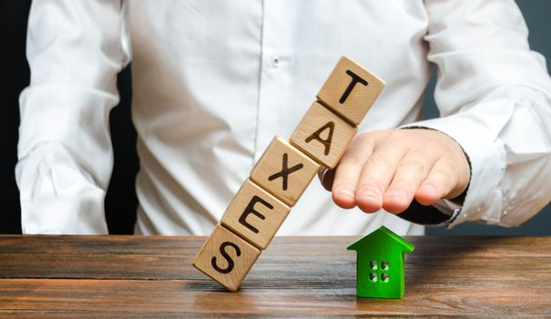 A man protects his hand with a figurine of a house from a falling tower of cubes with the word taxes. Heavy tax burden, protecting the interests of small and medium-sized businesses, competitiveness.
