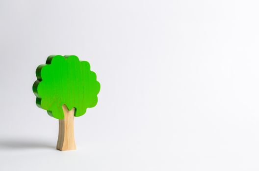 Toy wooden tree on a white background. Minimalism and the concept of environmental conservation. lungs of the planet. Family tree, a symbol of strength and wisdom. Illegal deforestation.