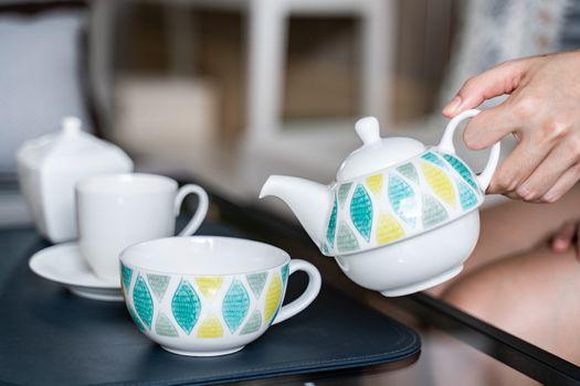hand holding pot pour tea into a cup.