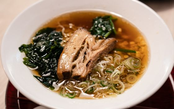Delicious Japanese ramen noodles with pork, and seaweed on bowl.