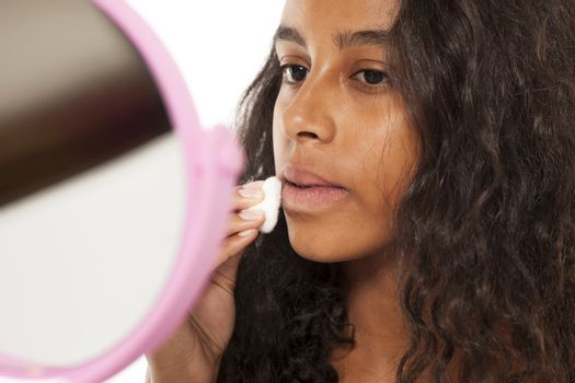 A young dark-skin girl remove her makeup