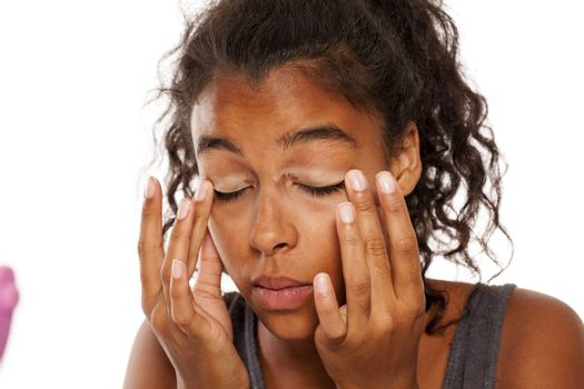 dark skinned woman applies a makeup base on the eyelids